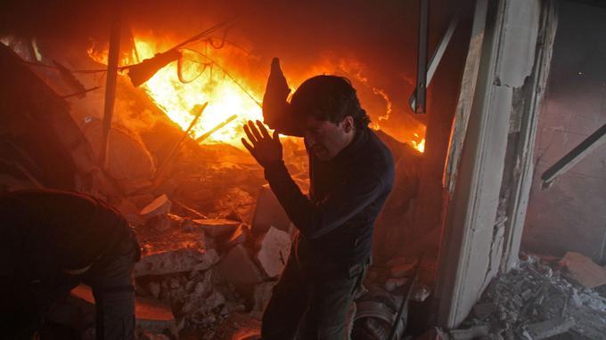 Un homme recherche des survivants dans un immeuble en feu après une attaque aérienne.