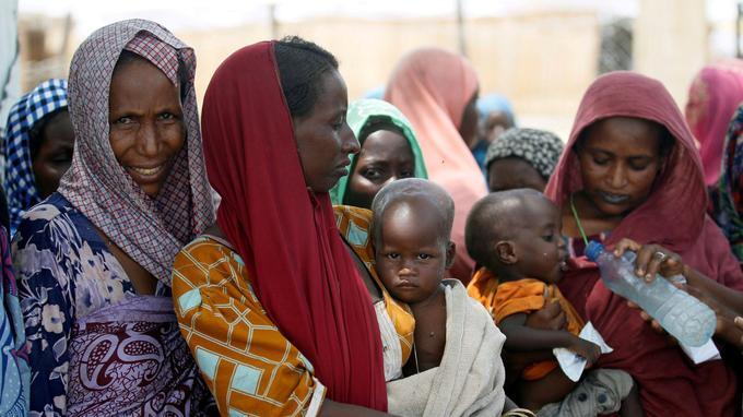Des femmes attendent avec leur enfant de recevoir des rations alimentaires dans un camp déplacé au Nigeria.
