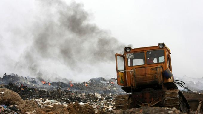 Un tracteur tente d'éteindre un tas de poubelles brûlant dans une décharge à Saburovo, à la périphérie de Moscou, le 19 août 2010.