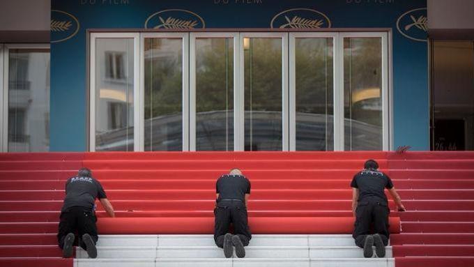 Des techniciens déroulent le tapis rouge du 71e Festival de Cannes sur les marches du Palais à l'occasion de la cérémonie d'ouverture. D'une soixantaine de mètres, le tapis rouge est changé trois fois par jour.