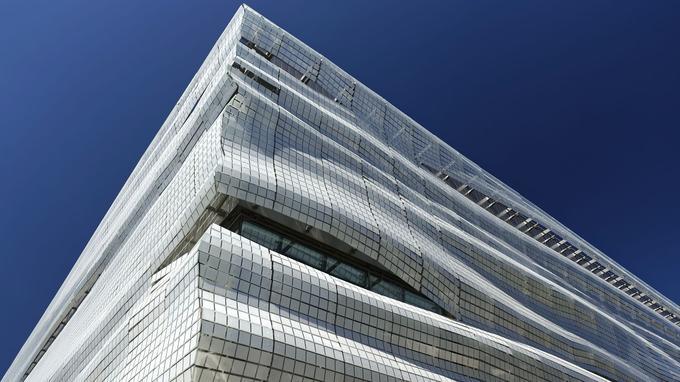 La façade carrée constituée de milliers de lames de verre sérigraphié rappelant le drapé d'une toge ou une mosaïque.