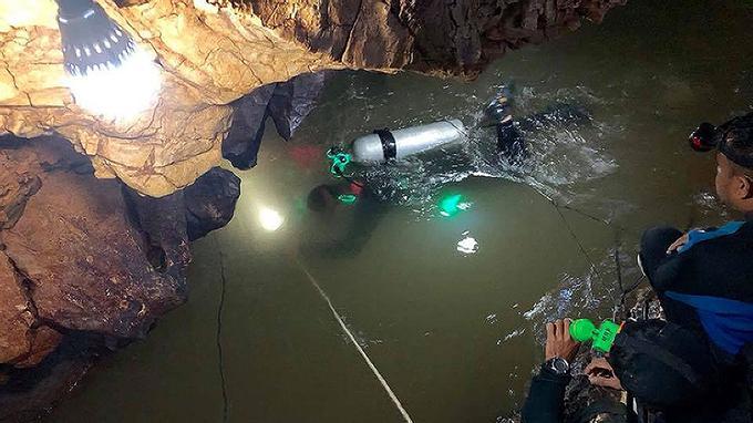 Les plongeurs SEAL de la Marine royale thaïlandaise inspectent le tunnel rempli d'eau dans la grotte.