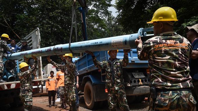 Soldats et secouristes installent des pompes afin de faire descendre l'eau qui se trouve dans la grotte.