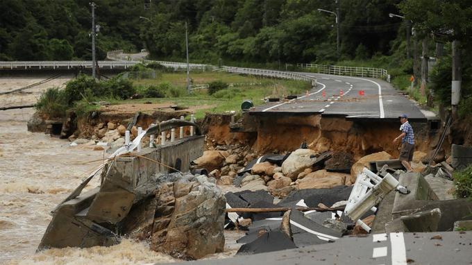 La route s'est effondrée à cause des fortes pluies à Higashihiroshima, dans la préfecture d'Hiroshima, le 7 juillet 2018. Trois personnes ont été retrouvées mortes près de rivières inondées par la pluie au Japon.