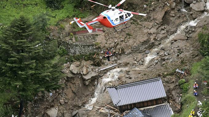 Un hélicoptère de sauvetage survole des bâtiments endommagés après un glissement de terrain à Iwakuni, dans la préfecture de Yamaguchi, dans le sud-ouest du Japon.