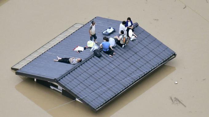 Les habitants attendent être secourus au sommet d'une maison presque submergée par les inondations à Kurashiki, préfecture d'Okayama, au sud-ouest du Japon.
