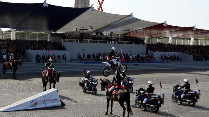 Un membre de l'Escadron motocycliste réalise un saut devant des Gardes républicains.