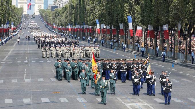 Des membres de la Compagnie Valdemoro d'Espagne et des élèves de l'École de Gendarmerie de Tulle marchent ensemble sur les Champs-Élysées.