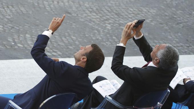 Le président français Emmanuel Macron et le premier ministre singapourien Lee Hsien Loong observent le défilé aérien, samedi sur les Champs-Élysées.