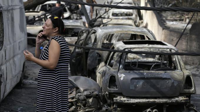 Une femme au milieu des carcasses de voitures calcinées, à Mati, mardi.
