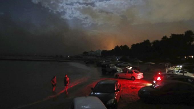 Des habitants se tiennent sur la plage à l'abri de voitures garées pour les protéger à Mati.