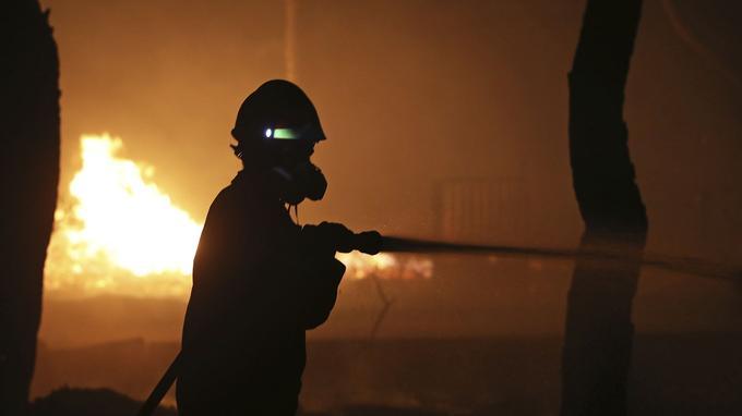 Un pompier tente de circonscrire les flammes à Mati, dans la nuit de lundi à mardi.