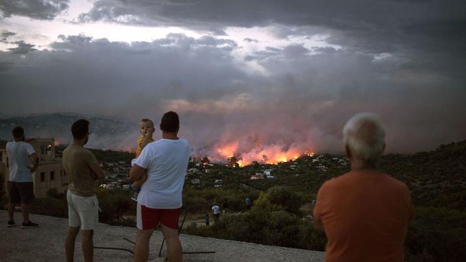 Des habitants observent depuis Rafina un incendie à proximité d'Athènes, lundi.