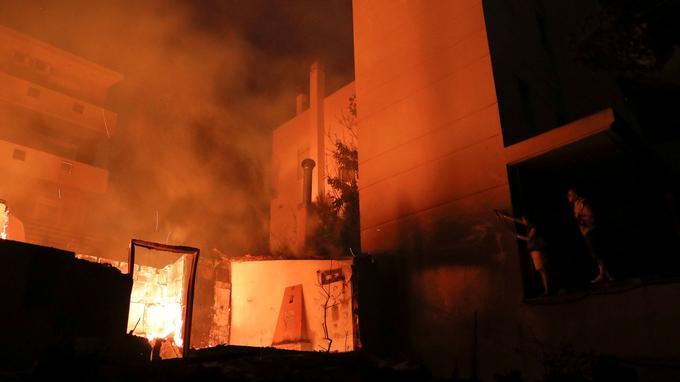 Des habitants tentent d'éteindre une maison en flammes à Mati.