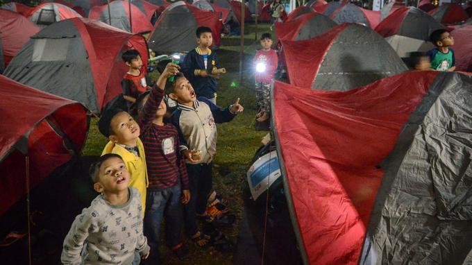 Des enfants indonésiens regardent la lune de sang en attendant une éclipse lunaire au camp de Salman Astro à Bandung