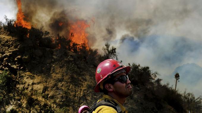 Un pompier regarde le feu de «Cranston» se développer à plus de 1 200 acres dans la forêt nationale de San Bernardino au-dessus de Hemet, en Californie, le mercredi 25 juillet 2018.