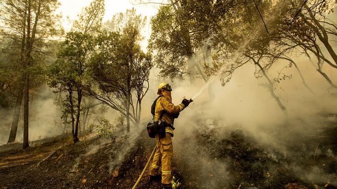 Le pompier Scott Brown pulvérise de l'eau lors d'un contre-feu alors qu'il combat l'incendie «Carr» à Redding, en Californie.