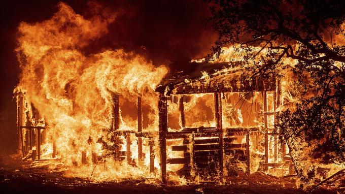 Dans cette photo du jeudi 26 juillet 2018, une structure brûle alors que le feu «Carr» roule le long de la route 299 près de Redding en Californie.