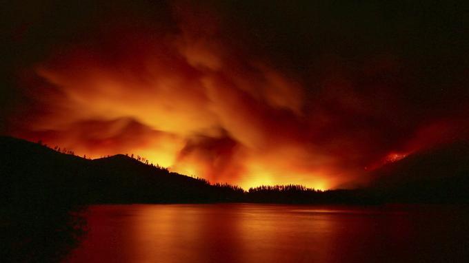 Sur cette photo prise mercredi 25 juillet 2018, un feu de forêt brûle près du lac à Whiskeytown, en Californie.