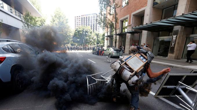 Un contre-manifestant renvoie un fumigène lancé par la police.