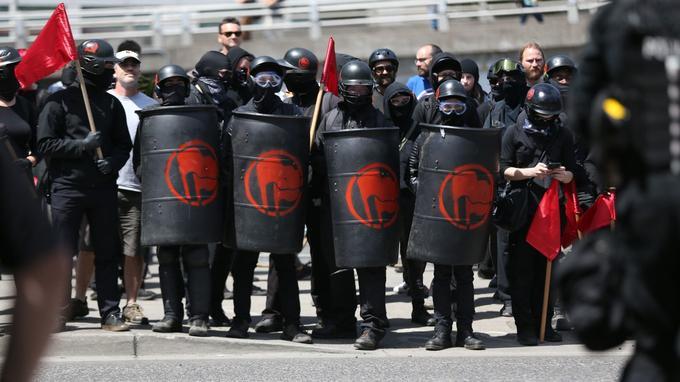 Des militants antifascistes étaient également casqués et masqués, et équipés de boucliers ornés d'un logo antifasciste.