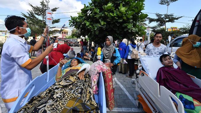 Des centaines de blessés portant des traces de sang sont traités à l'extérieur d'un hôpital endommagé de Mataram, principale ville de Lombok très affectée par le séisme.