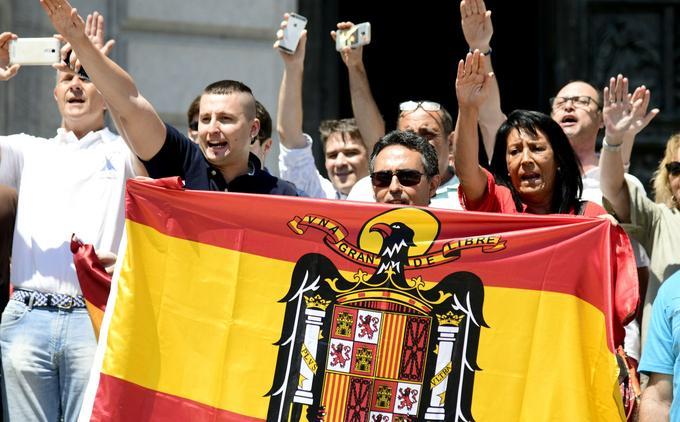 Des manifestants opposés au transfert des restes de Franco font le salut franquiste en brandissant un drapeau de l'Espagne franquiste devant la Basilique du Valle de Los Caidos, le 15 juillet.
