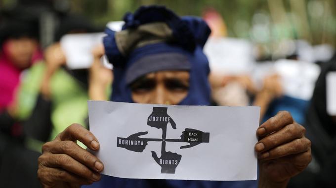 Une femme réfugiée rohingya brandit une pancarte alors qu'elle participe à une manifestation au camp des réfugiés de Kutupalong pour marquer le premier anniversaire de leur exode à Cox's Bazar, dans l'extrême sud-est du Bangladesh.