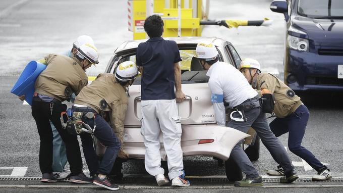 Des personnes évacuent un véhicule endommagé à Osaka pour rétablir la circulation.