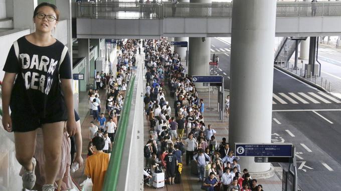 Des passagers attendent un bus spécial à l'aéroport international de Kansai, après le passage du puissant typhon Jebi à Osaka.