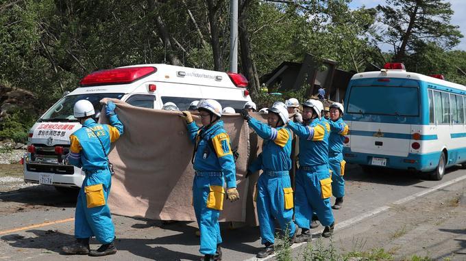 Des secouristes transportent une victime dans une ambulance à Atsuma, une ville du district de Hokkaido affectée par des glissements de terrain.