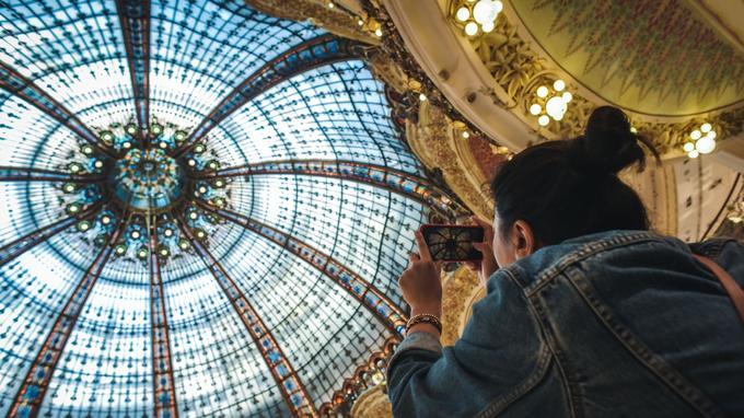Une visiteuse prends en photo la coupole Art Nouveau à l'intérieur des Galeries Lafayette Boulevard Haussman lors des Journées Européennes du Patrimoine à Paris le 16 septembre 2018.Photo : Lucas Barioulet pour le Figaro