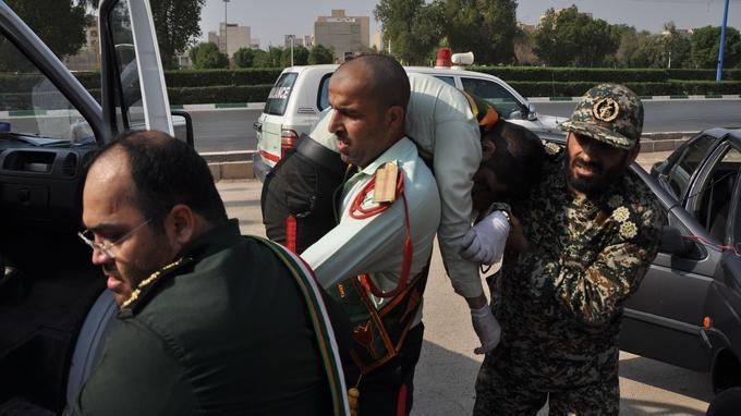 Un membre de la garde révolutionnaire évacue l'un de ses camarades blessé après un attentat pendant les commémorations du 38e anniversaire de l'invasion de par l'irak de l'Iran, le 22 septembre à Ahvaz.