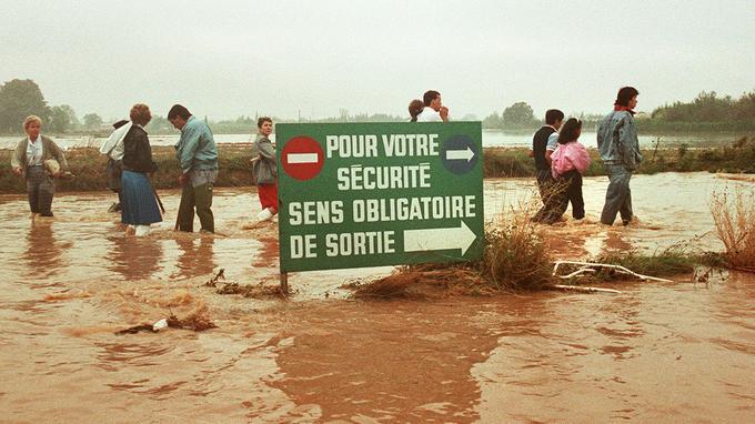 Des Nîmois marchent dans l'eau boueuse pour aller se mettre à l'abri, le 3 octobre 1988. La catastrophe a fait 50.000 sinistrés.