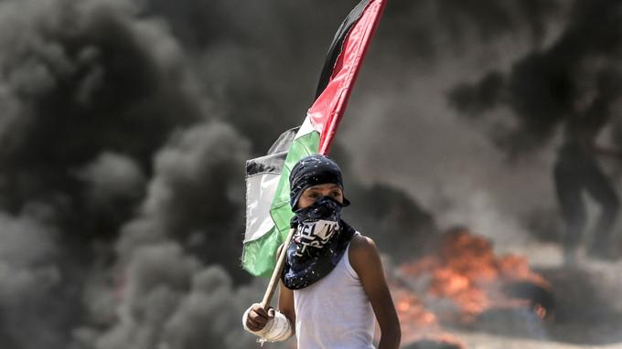 Un garçon palestinien tenant son drapeau national observe les affrontements avec les forces de sécurité israéliennes dans la bande de Gaza, le 14 mai 2018.