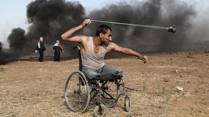 Saber al-Ashkar, un Palestinien de 29 ans, lance des pierres lors d'affrontements avec les forces israéliennes le long de la frontière de la bande de Gaza, à l'est de la ville, le 11 mai 2018. Les Palestiniens manifestaient contre le transfert à Jérusalem de l'ambassade américaine en Israël.