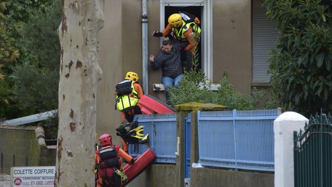 Des pompiers aident une habitante à évacuer son habitation, jeudi, à Trèbes.