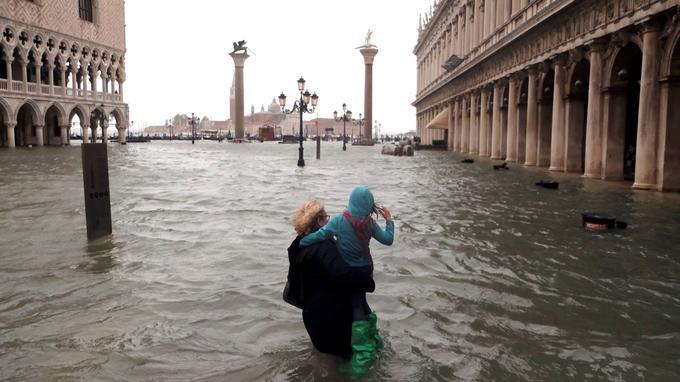 Une femme porte son enfant sur la place Saint-Marc, à Venise.