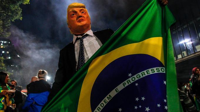 Un partisan de Jair Bolsonaro arbore un drapeau brésilien tout en portant un masque du président des États-Unis Donald Trump, dimanche à Sao Paulo.