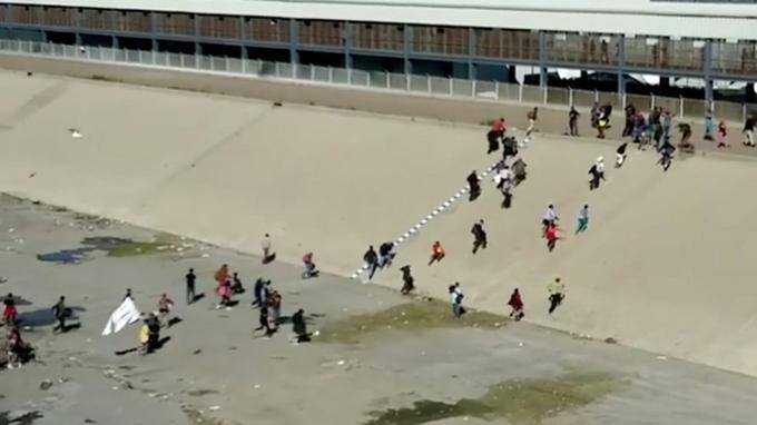 Des membres de la «caravane» courent vers la frontière avec les États-Unis, à Tijuana au Mexique, dimanche 25 novembre.