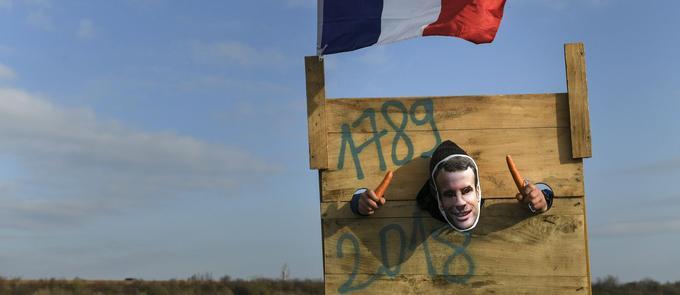 À Dole (Jura), le 17 novembre, un manifestant portant un masque d'Emmanuel Macron pose dans la réplique d'une guillotine.
