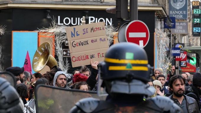 Aux abords des grands magasins ce samedi 8 décembre. Cette pancarte rappelle, à nouveau, l'arrestation de dizaines de jeunes jeudi à Mantes-la-Jolie, filmée à genoux.