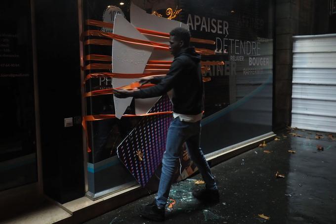 À Tours, un homme tente, avec les moyens du bord, de réparer une vitrine cassée lors de la manifestation du 8 décembre.