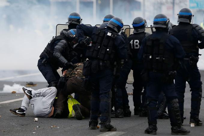 Des forces de l'ordre arrêtent des manifestants, sur les Champs-Élysées.