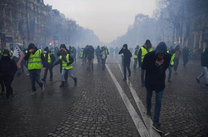 Des «gilets jaunes» cherchent à fuir les gaz lacrymogènes des forces de l'ordre, sur les Champs-Élysées à Paris, ce samedi 15 décembre en fin de journée.