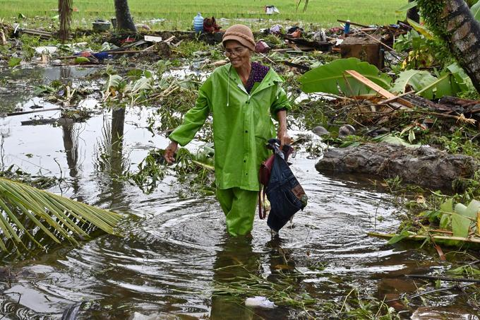Une Indonésienne récupère des objets de sa maison dévastée à Carita, le 24 décembre.