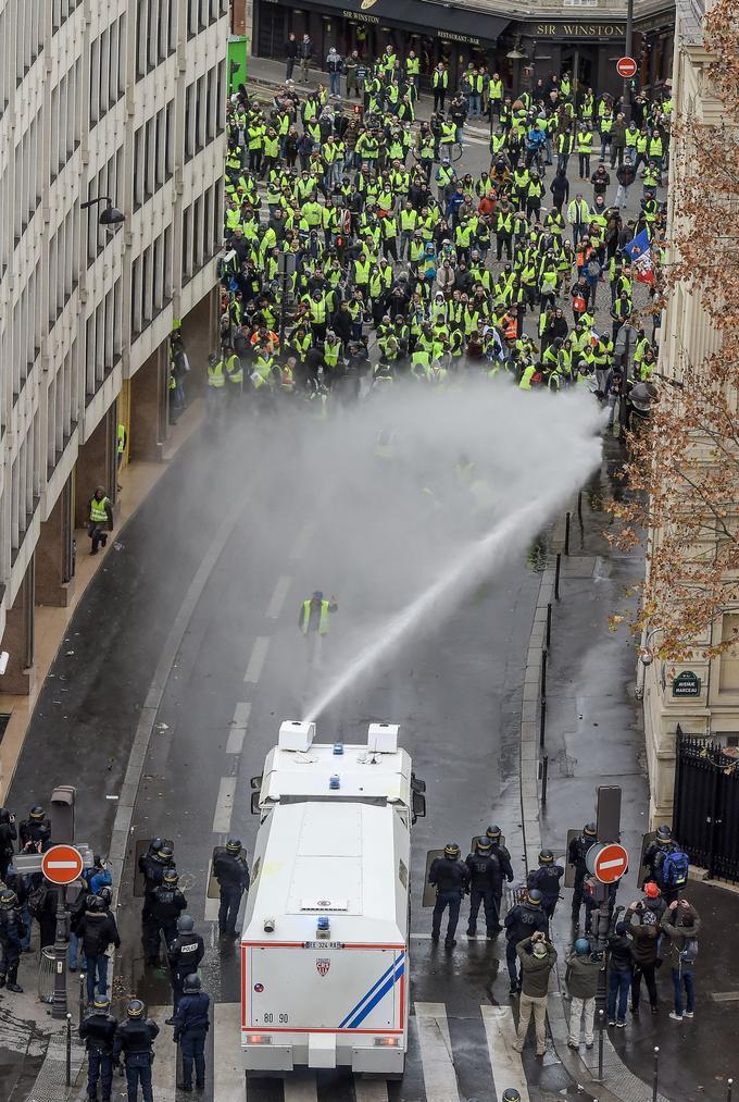 Les «gilets jaunes» et les CRS se font face à proximité de l'Arc de Triomphe lors du quatrième samedi de mobilisation.