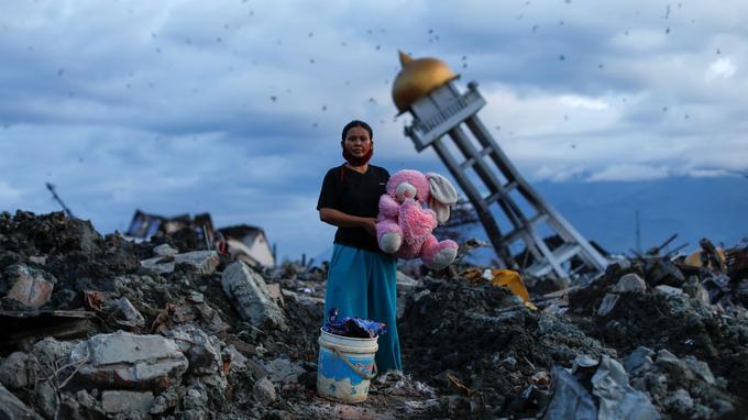 Une femme ayant perdu ses trois enfants après le séisme en Indonésie se tient au milieu des décombres.