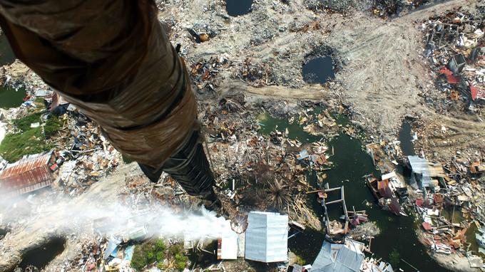 Un désinfectant est aspergé à travers une zone affectée par la liquéfaction du sol, où des corps pourraient être enfouis.