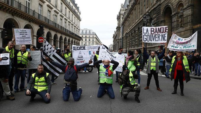 Près du Louvre, à Paris, des manifestants brandissent des pancartes le 22 décembre, lors de l'acte VI.
